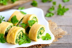 Eggs omelet rolls with cheese and greens on a plate and a vintage wooden table. Delicious stuffed omelet appetizer. Country style. Omelette rolls. Egg omelet Stock Photography