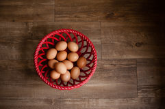 Eggs in one basket. Brown speckled eggs in red ceramic basket on farmhouse wooden floor, food ingredients Stock Photos