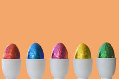 Easter Eggs in a row with egg cups, orange background, copy space Stock Images