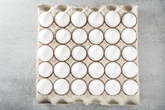 Eggs packed in cardboard or boxes for transporting. White fresh chicken eggs and one brown egg in a carton box isolated on yellow background. Top view with copy stock photos