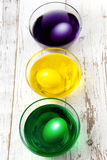 Eggs in paint cups Stock Photography