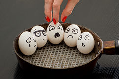 Eggs with painted emotions in a frying pan, a female hand takes one of them. Stock Photo