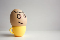 Eggs with painted face. Concept. Of reaching a goal, an egg in a coffee cup photo for your design stock images
