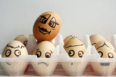 Eggs with a painted face in two rows. Transparent container. Photo for your design. One egg from above stock image