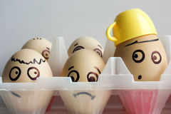 Eggs with a painted face in two rows. Transparent container. Photo for your design. One egg in a cup of coffee and yellow royalty free stock photo