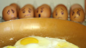Eggs with painted faces look on the pan stock video footage