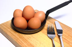 Eggs in a pan with and fork and knife Stock Photography