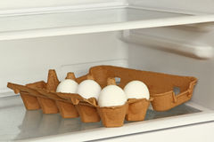 Eggs in a paper box on refrigerator shelf. Stock Photos
