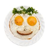 Breakfast for kids. Kids funny meal on white plate. Eggs, parsley vegetables/bread/ketchup is formed by a funny face on a white plate. The concept of food for Royalty Free Stock Image