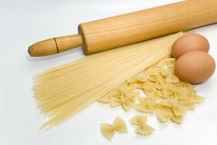 Eggs and pasta. Pasta spaghetti with eggs and kitchen tools over white background Royalty Free Stock Photos