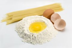 Eggs, pasta and flour. An egg in a pile of flour preparing for baking with pasta and eggs on the sides Royalty Free Stock Photos