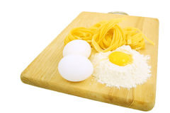 Eggs, pasta and flour on wooden desk isolated Stock Photos