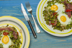 Eggs with peas and ham. Two eggs with peas and ham two plates on the table Stock Image