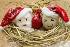 Eggs with persons in the nest for Christmas. Happy eggs with persons in the nest for Christmas Royalty Free Stock Images