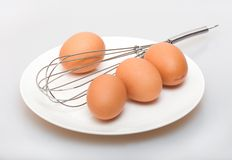 Eggs on a plate and whisk Royalty Free Stock Photos