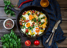 Eggs poached with vegetables,named. Shakshouka on wooden table Stock Images
