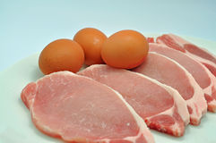 Eggs and pork chops. Eggs with raw pork chops close up shot Royalty Free Stock Photo