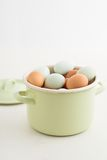Eggs in a pot. Fresh light green eggs from Easter egger chicken and brown eggs in a light green pot royalty free stock image