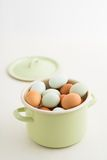Eggs in a pot. Fresh light green eggs from Easter egger chicken and brown eggs in a light green pot Royalty Free Stock Photo