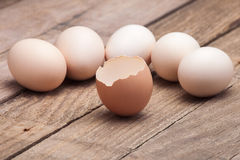 The eggs put on a small group. On a wooden table from old boards and the cracked egg from above nobody Stock Photo
