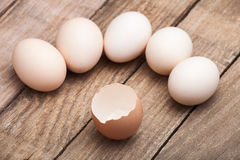 The eggs put on a small group. On a wooden table from old boards and the cracked egg from above nobody Royalty Free Stock Image