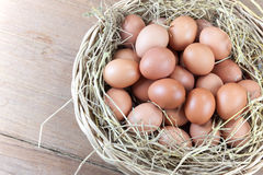 Eggs in a rattan basket. With straw secondary on wood background Royalty Free Stock Image