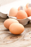 Eggs. Raw eggs on wood with eggs in a carton as a background, raw fresh cooking produce, ingredient, chicken eggs Stock Photos