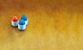 Eggs red blue green turquoise on white bowls on a wooden panorama background. Three painted eggs red blue green turquoise on white bowls on a wooden panorama Royalty Free Stock Images