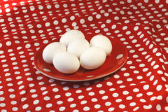 Eggs on a red plate on red background Stock Photography