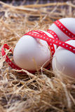 Eggs with a red ribbon on the hay for easter Stock Images