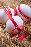Eggs with a red ribbon on the hay for easter Royalty Free Stock Photos