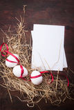 Eggs with a red ribbon on the hay for easter Royalty Free Stock Images