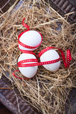 Eggs with a red ribbon on the hay for easter Stock Image