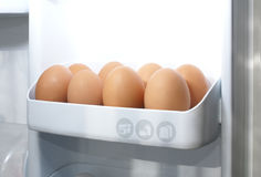 Eggs in refrigerator. Beige eggs in refrigerator full of light stock photo