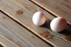 Eggs on a rough table. Two eggs on a rough brown table stock photos