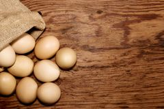 Eggs in sackcloth bag on wooden table Royalty Free Stock Image