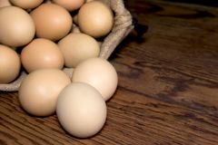 Eggs in sackcloth bag on wooden table,selected focus Stock Image