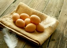 Eggs on a sacking lay on old wooden Royalty Free Stock Photos