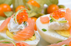 Eggs with salmon and caviar. Egg halves with smoked salmon and trout caviar on cream cheese, decorated by lime peel strips Stock Photos