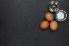 Eggs with salt and oil at the right upper corner on a dark slate Royalty Free Stock Photo