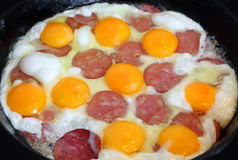 Eggs and sausage fried on a pan Stock Images