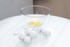 Eggs in the shell near the bowl with a broken egg Royalty Free Stock Images