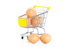 Eggs and shopping trolly isolatedon white background Royalty Free Stock Photography