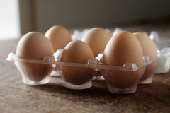 Eggs. Six eggs in a container above a wooden table Stock Photo
