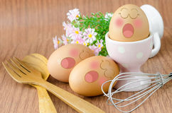 Eggs sleep with Expression Face in white cup and flower. Royalty Free Stock Photography