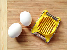 Eggs and slicer Stock Images