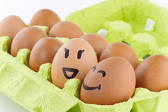 Eggs with smiley faces in eggbox. Open eggbox with smiley faces isolated on white background Royalty Free Stock Photography