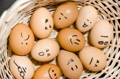 Eggs with smiling faces in the basket stock photography