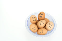 Eggs with smiling happy faces on plastic bowl, isolated on white background.  Stock Photography