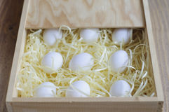 Eggs on a soft substrate in a wooden box. White eggs on a soft substrate in a wooden box. Luxury package Stock Image